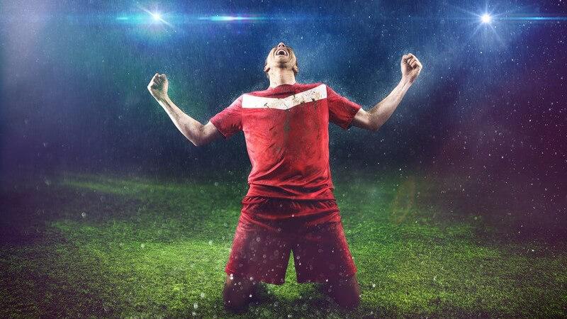 Fußballspieler in rotem Trikot kniet im Regen und unter Flutlicht auf dem Rasen und jubelt
