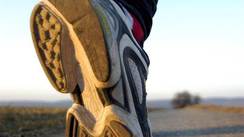 Ansicht von unten: Laufschuh eines Joggers auf Straße