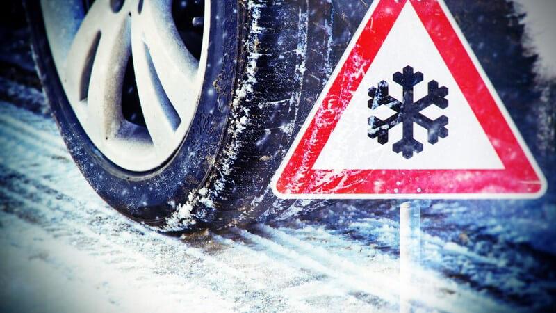 Autoreifen auf schneebedeckter Fahrbahn, davor ein Schnee-Warnschild (Fotomontage)