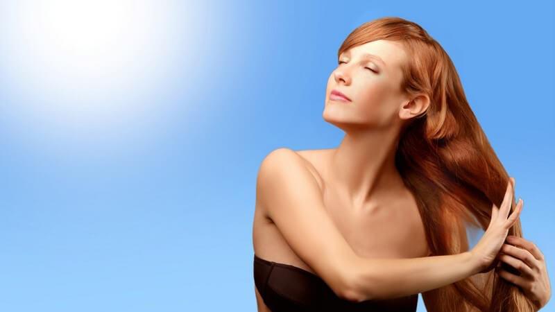 Junge Frau mit langen roten Haaren im Bikini unter blauem Himmel mit Sonnenschein