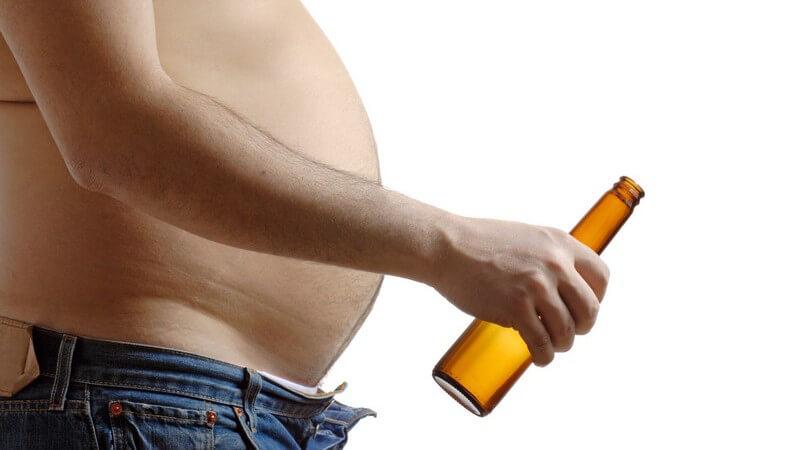 Nahaufnahme Mann mit Bierbauch und offener Hose mit leerer Bierflasche in Hand