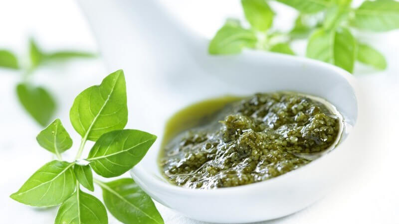 Italienisches grünes Pesto (Pesto alla genovese) in weißem Gefäß mit Basilikum-Blättern vor weißem Hintergrund