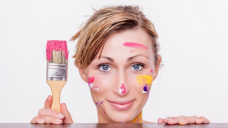 Frau mit von Farbe verschmiertem Gesicht schaut unter einem Tisch hervor und hält einen Farbpinsel in der Hand