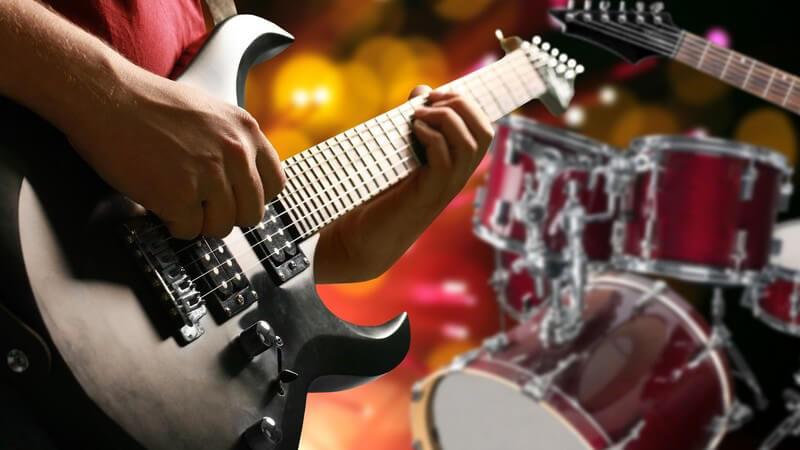 Gitarrist einer Band spielt auf einer schwarzen E-Gitarre, im Hintergrund ein rotes Schlagzeug