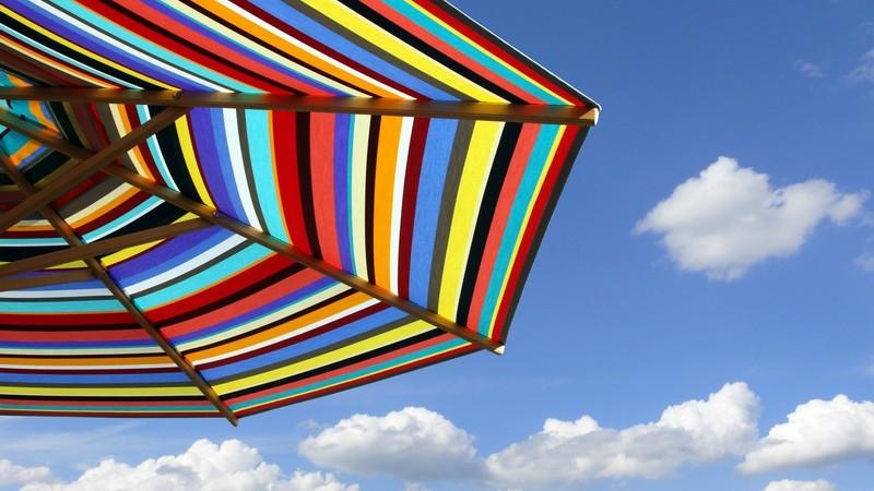 Aufgeschlagener Sonnenschirm unter blauem Himmel