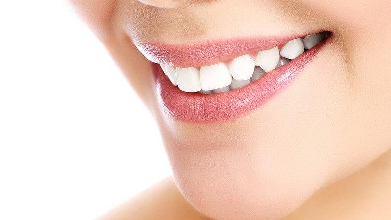 Nahaufnahme der Mundpartie einer lächelnden jungen Frau mit weißen Zähnen und schöner Haut, weißer Hintergrund