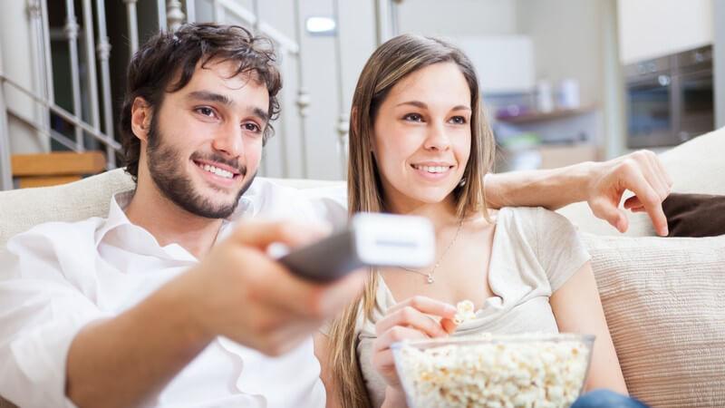 Paar guckt Fernsehen, er hält die Fernbedienung und sie das Popcorn