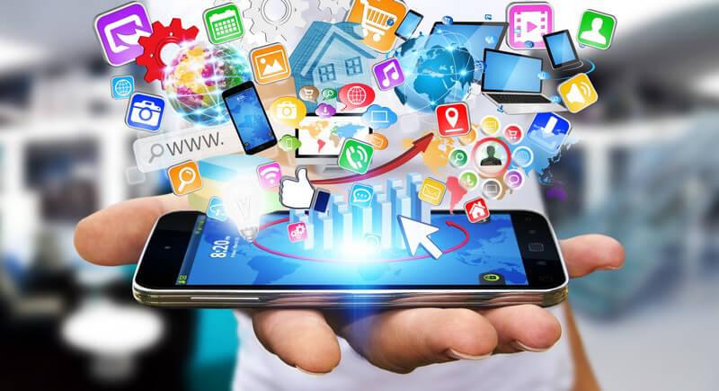 Hand hält ein Smartphone, aus dem viele bunte Icons kommen (Fotomontage)