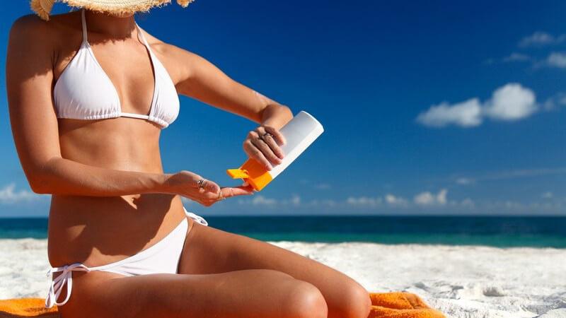 Frau mit Strohhut im weißen Bikini am Strand beim Eincremen mit Sonnenmilch