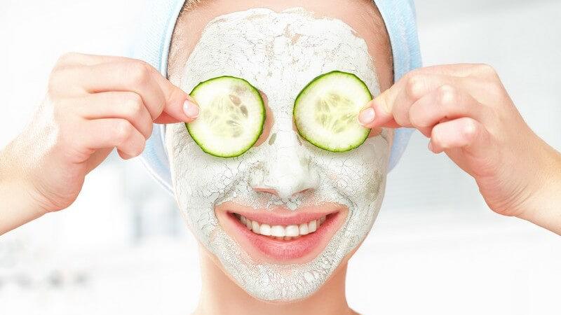 Lächelnde Frau mit heller Gesichtsmaske hält sich Gurkenscheiben vor die Augen