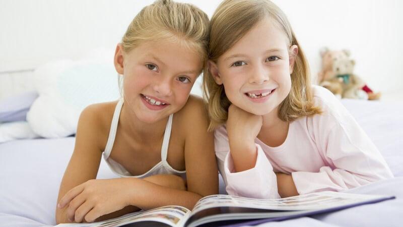 Zwei befreundete Mädchen im Schlafanzug liegen mit Buch zusammen im Bett, lächeln in Kamera