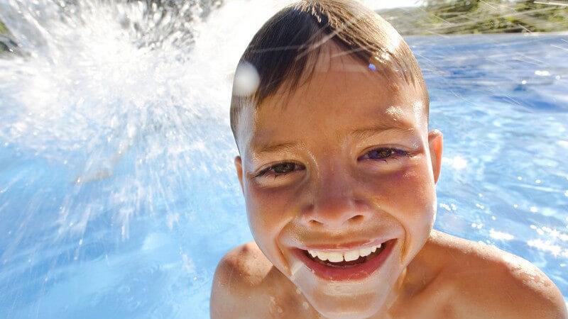 Junge im Swimmingpool lacht in Kamera, im Hintergrund spritzendes Wasser