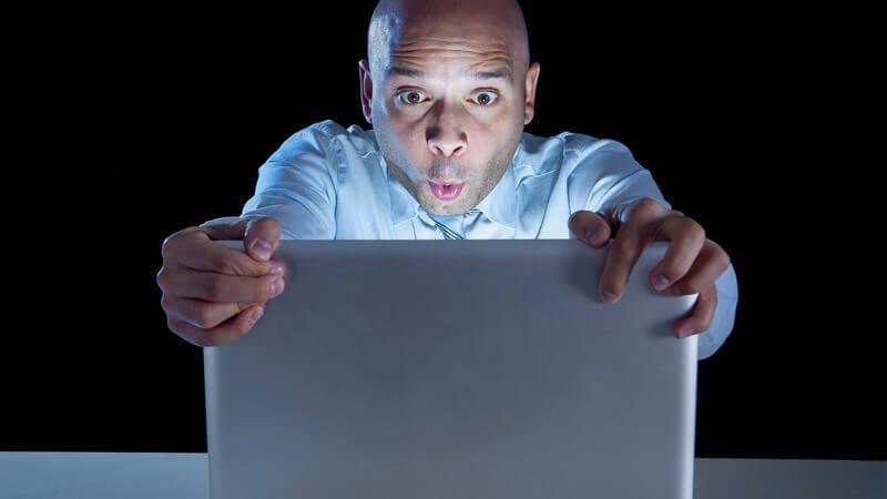 Kahlköpfiger Businessmann sitzt in dunklem Raum vor dem Laptop und hält ihn gespannt fest