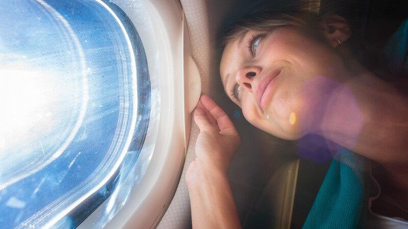 Junge Frau blickt glücklich durch ein Fenster im Flugzeug, die Sonne scheint hindurch
