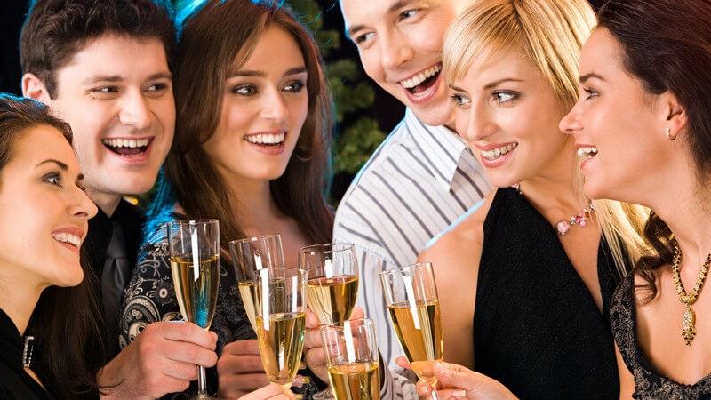 Sechs lachende Freunde in festlicher Kleidung stoßen mit Glas Sekt an