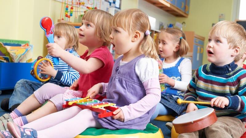 Kleine Kindergartenkinder beim Musizieren in der Gruppe