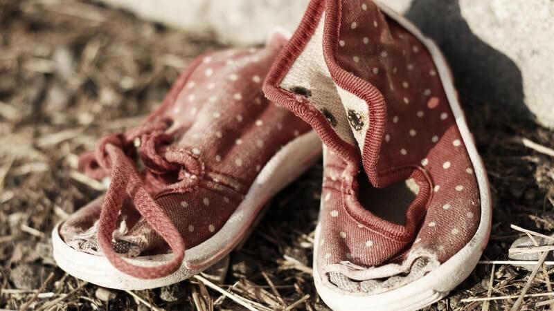 Rote Kinderschuhe liegen im Dreck, total kaputt