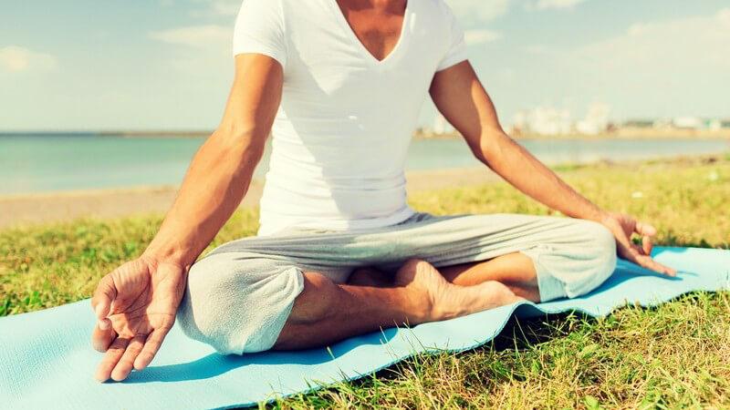 Mann in weißem V-Shirt meditiert auf einer Yogamatte auf einer Wiese direkt am Meer