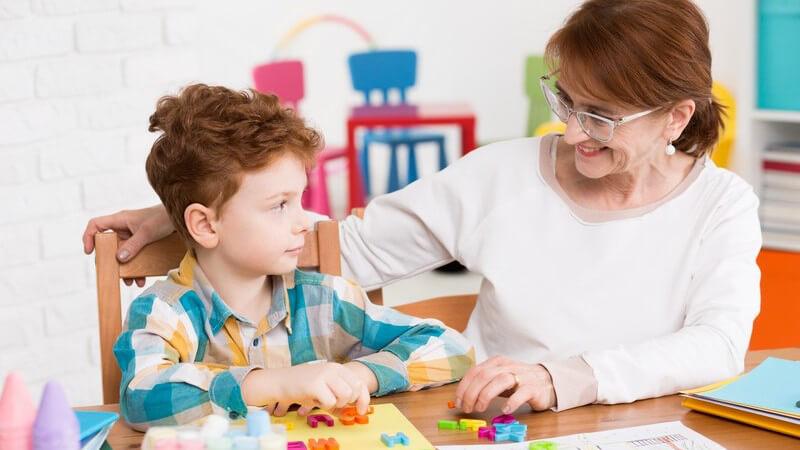 Junge sitzt neben älterer Lehrerin mit Brille an einem Tisch und lernt mit bunten Plastikbuchstaben