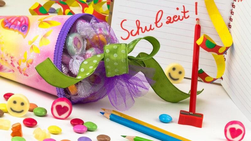 Einschulung, erster Schultag: Schultüte mit Süßigkeiten, drumherum bunte Stifte