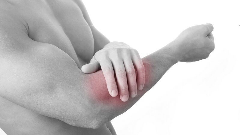 Schwarz-weiß Bild Mann mit Armschmerzen hat Hand auf rot beleuchteten Arm gelegt
