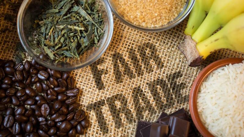 """Fair gehandelte Lebensmittel wie Kaffeebohnen, Bananen und Reis auf Jutesack mit der Aufschrift """"FAIR TRADE"""""""