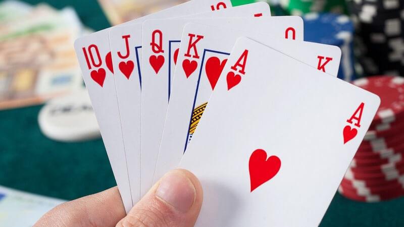 """Hand hält fünf Pokerkarten mit einem """"Royal Flush"""", im Hintergrund liegen Geldscheine und Poker-Chips"""