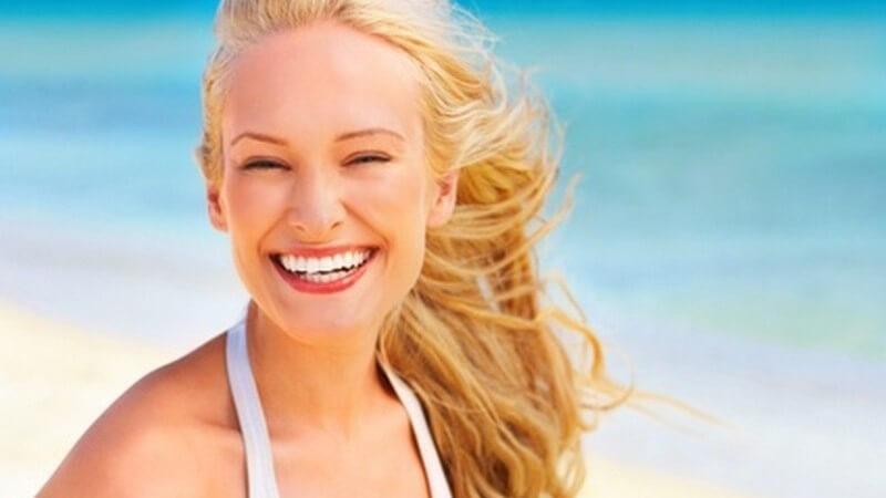 Junge, lächelnde blonde Frau mit weißem Bikini am Strand vor azurblauem Meer