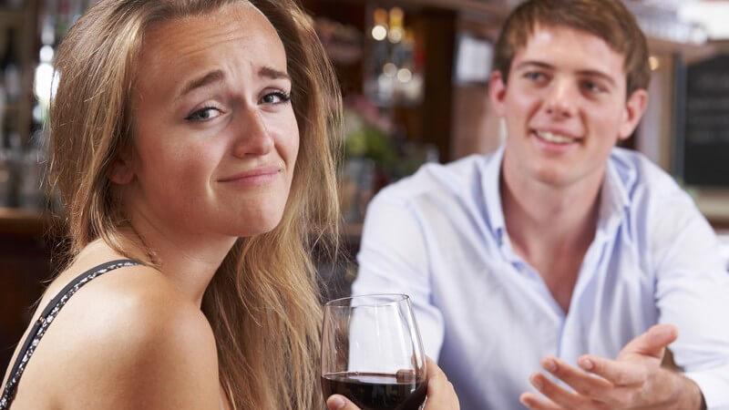 Zwei junge Leute bei einem Blind-Date, sie schaut enttäuscht und abgeneigt in die Kamera und hält ein Glas Rotwein