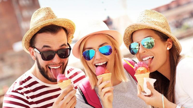 Drei Freunde mit Sonnenhut und Sonnenbrille essen ein pinkes Eis