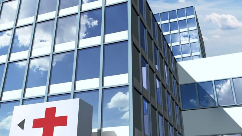 Krankenhaus mit spiegelnden Glasfronten und großem roten Kreuz