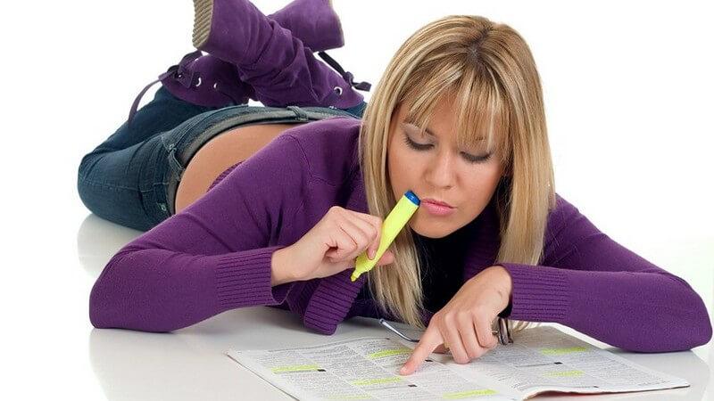 Junge blonde Frau liegt auf Boden mit Textmarker auf Zeitung, Jobsuche, Arbeitslosigkeit, sucht Jobangebote in Inseraten