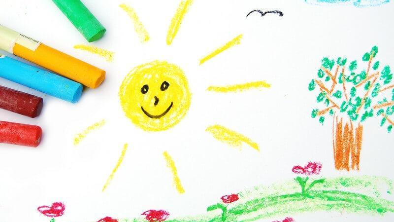Kindergemälde Sonne mit Wiese, daneben Wachsmalstifte