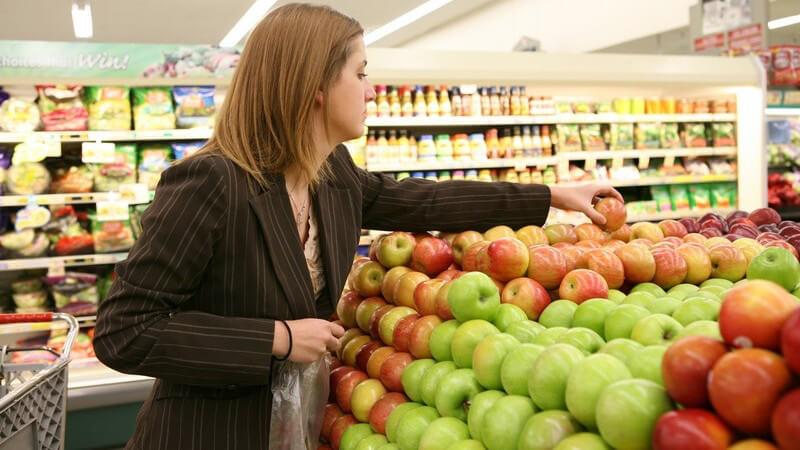Junge Frau im Supermarkt in Obstabteilung sucht sich Äpfel raus