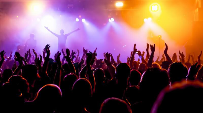 Blick über die jubelnde Menge hin zur Bühne eines Konzerts