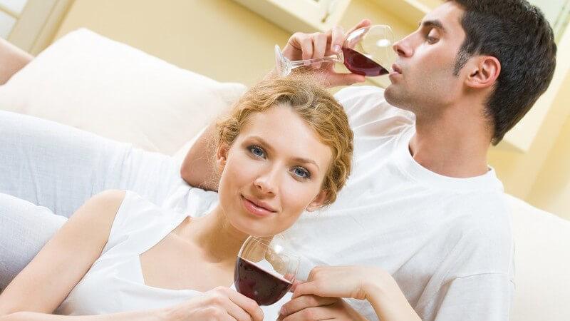 Junges Paar auf Couch mit Rotwein