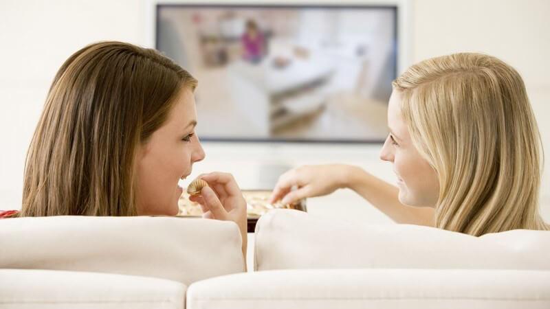 Rückenansicht zwei Freundinnen auf Couch vor Fernsehen essen Pralinen