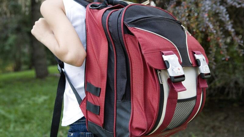 Junge Schülerin trägt großen und schweren Rucksack