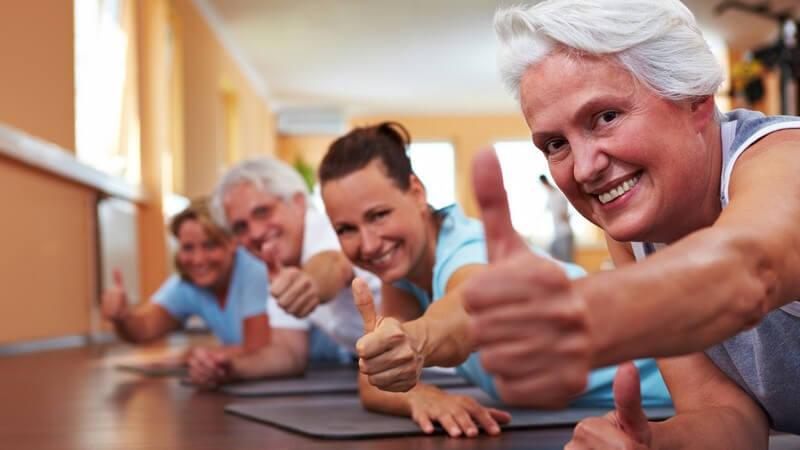 Junge und ältere Menschen im Fitnessstudio auf Gymnastikmatten