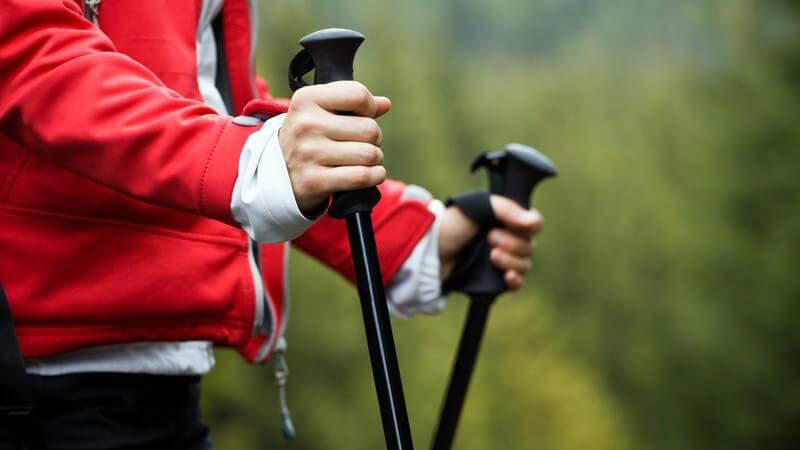 Frauenhände halten Nordic-Walking-Stöcke