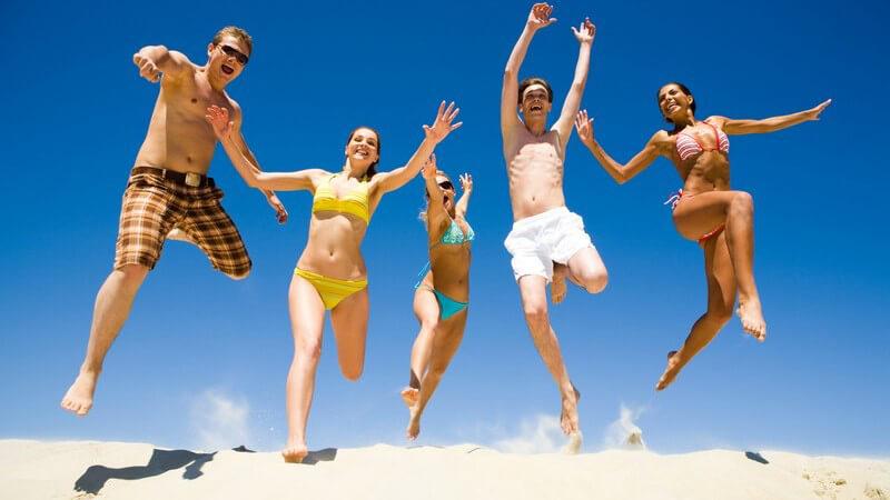 Fünf Jugendliche in Badehose und Bikini springen auf Sand vor blauem Himmel in die Luft