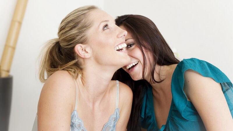 Zwei Freundinnen sitzen lachend nebeneinander