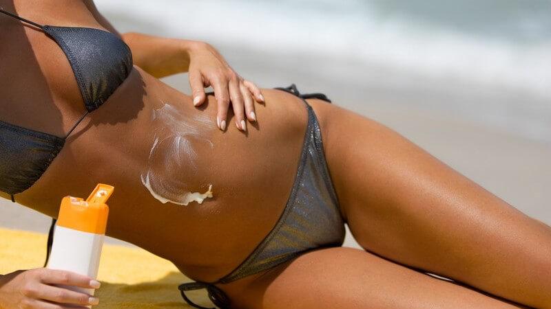 Frau im Bikini am Strand cremt sich mit Sonnencreme ein, im Hintergrund Meer