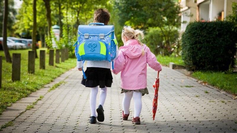 Rückenansicht Mädchen mit Schultasche an ihrem ersten Schultag mit kleinerer Schwester an der Hand