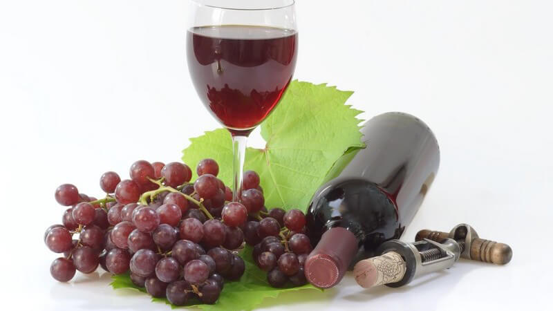Glas mit Rotwein, dunkle Weintraube, liegende Flasche Rotwein und Korkenzieher