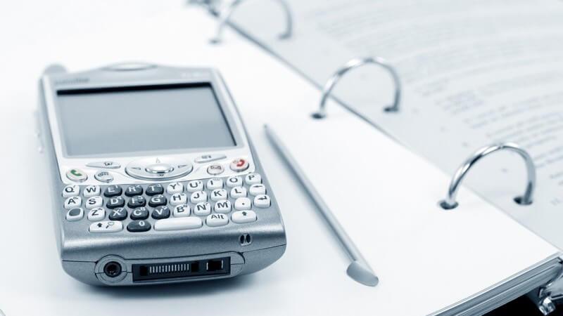 Silberner PDA Organizer oder Handy mit Stift auf Terminplaner oder Mappe