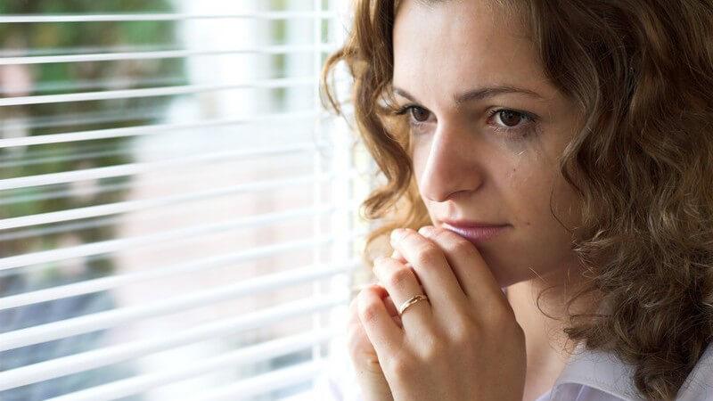 Junge Frau mit verweinten Augen steht besorgt am Fenster