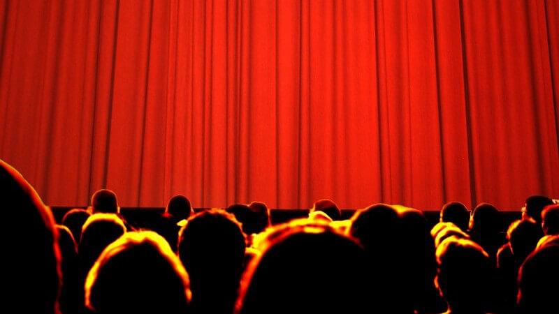 Rückansicht Köpfe einer großen Menge vor geschlossenem roten Vorhang, Kino, Theater