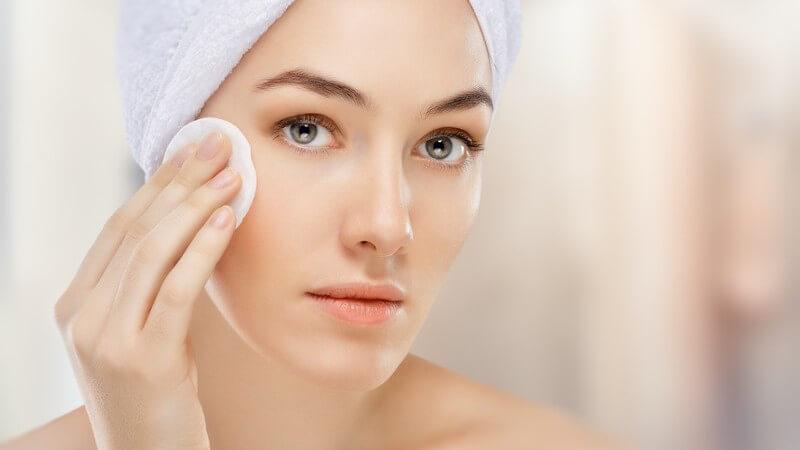 Frau mit Handtuch im Haar wischt mit einem Kosmetikpad über ihre Wange
