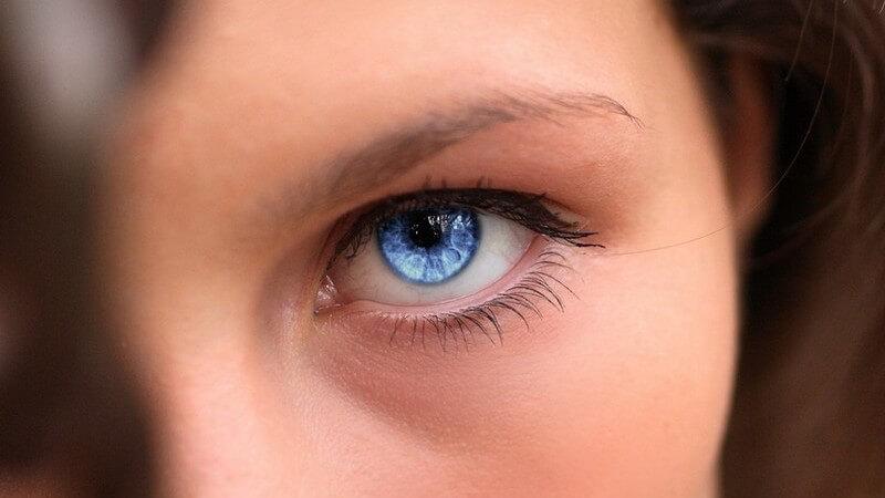 Blaues, weibliches Auge im Mittelpunkt, rechts brünette Haarsträhne hinterm Ohr